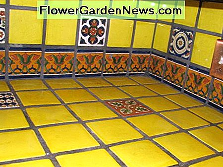 Yellow talavera tile kitchen countertop with border and single pattern tiles.