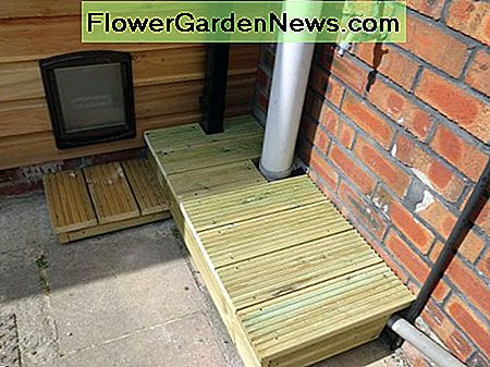 Decking planter platform and cat step used to hide downpipe from conservatory to drain.