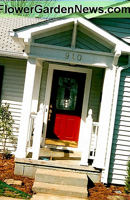 A pop of red makes this front door a focal point on a small cottage.