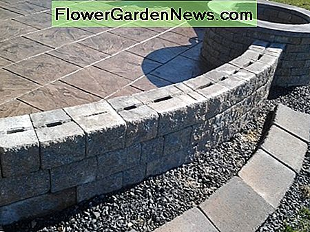 Masonry fire pit situated in a retaining wall.
