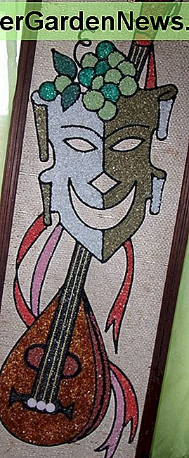 This is a 1960s vintage mid century modern pebble or gravel art. It is a comedy mask with a lute. It is 24