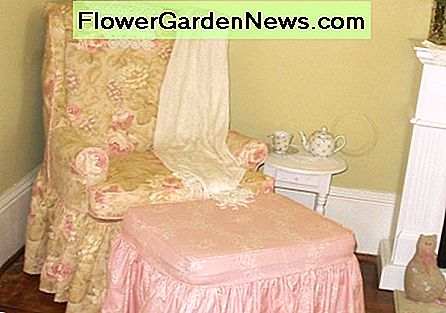 My daughter had a slipcover made for this chair in a vintage cabbage rose fabric and the footstool is covered in a floral design that coordinates.