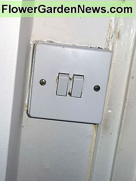 The old white plastic light switch for controlling the stairs lighting