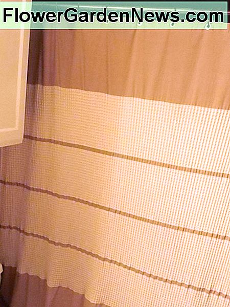 Waffle weave shower curtain adds cozy warm texture to the bathroom.
