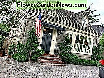 With brick steps and bay window, two dormer windows, and an American flag.