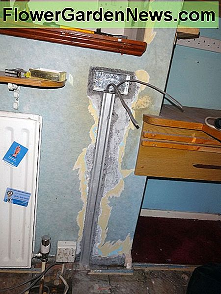 Metal back box for socket fitted in place and protective cover over cables in wall.